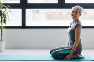 Woman sitting on pilates mat
